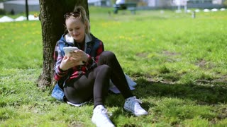 Girl sitting in the park and using tablet