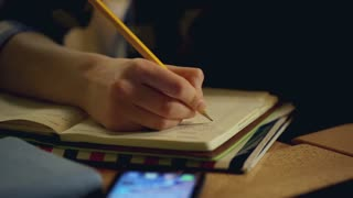 Girl sitting in the restaurant and writing something in journal