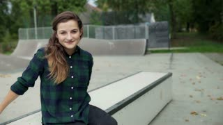 Girl sitting in the skate park and smiling to the camera