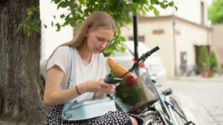Girl sitting next to her bicycle and texting on smartphone
