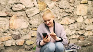 Girl sitting next to the brick wall and texting on smartphone