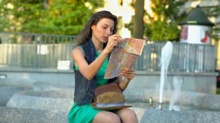 Girl sitting next to the fountain and checking direction on map