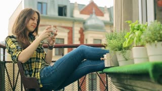 Girl sitting on balcony and texting on smartphone