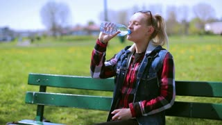 Girl sitting on the bench and drinking water