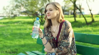 Girl sitting on the bench in park and drinking water