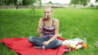 Girl sitting on the blanket in the park and smiling to the camera