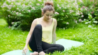 Girl sitting on the exercising mat in the park and looking very tired