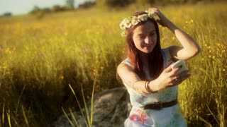 Girl sitting on the meadow with grommet and doing selfie