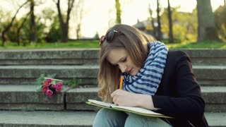 Girl sitting on the stairs and writing something in notebook