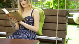 Girl sitting on the wooden swing and reading a book, steadycam shot