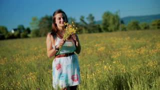 Girl smelling flowers on the meadow and smiling to the camera