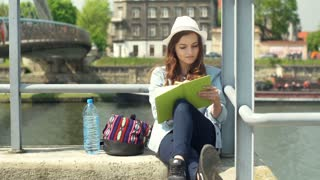 Girl smiling to the camera and writing something in notebook on the bridge