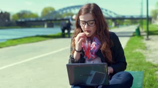 Girl smiling to the camera while eating biscuit and using laptop