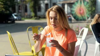 Girl smiling to the camera while eating yogurt and using tablet, steadycam shot