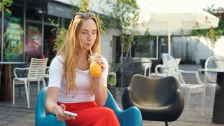 Girl smiling to the camera while texting on smartphone and drinking juice
