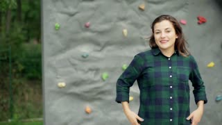 Girl standing against climbing wall and smiling to the camera