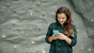 Girl standing against climbing wall and texting on smartphone