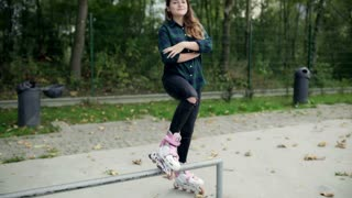Girl standing and wearing rollerblades in skate park, steadycam shot
