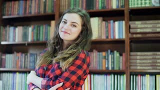 Girl standing in the library and smiling to the camera