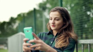 Girl standing next to the fence and doing selfies on smartphone