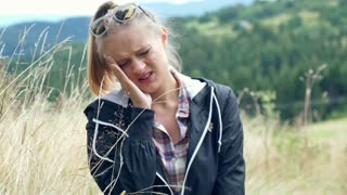 Girl standing on the hill in the meadow and have a headache