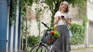 Girl standing with her bicycle and checking shopping in the basket