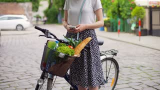 Girl standing with the bicycle on pathway and texting on smartphone