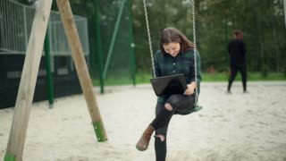 Girl swinging on the seesaw and holding laptop