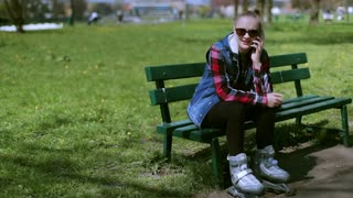 Girl talking on cellphone in the park and wearing rollerblades