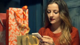 Girl talks about present on cellphone while sitting in the cafe at christmas eve