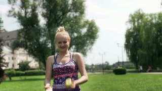 Girl throwing apple in the air and smiling to the camera in the park