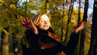 Girl throwing leaves and relaxing, slow motion shot