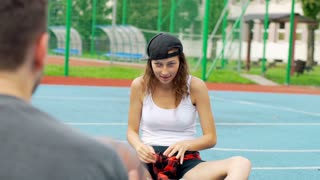 Girl throwing to someone ball and enjoying it on the sports field