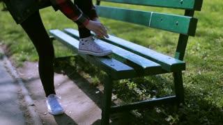 Girl tying shoe laces in the park