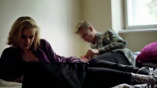 Girl using laptop and boy reading book while lying on the bed