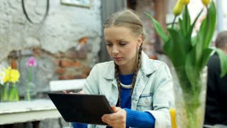 Girl using tablet in the outdoor cafe and smiling to the camera