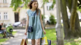 Girl walking with her shopping bags in the park and looking upset