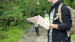 Girl walking with sticks in the forest while boy reading map, steadycam shot