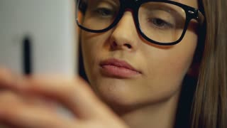 Girl wearing glasses and texting on her smartphone