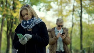 Girl wearing gloves and typing on smartphone in the park