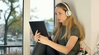 Girl wearing headphones and watching funny video on tablet