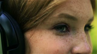 Girl wearing headphones and wink to the camera, closeup, steadycam shot