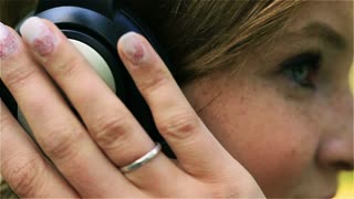 Girl with rosy cheeks listening music on headphones, closeup, steadycam shot
