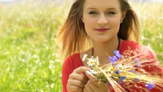 Girl with wreath of flowers sitting on the field and looking to the camera, stea