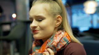 Girl wrapping her neck with a scarf because of sore throat