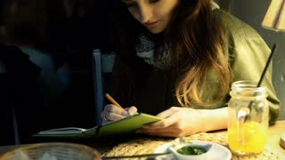 Girl writing in journal and looking to the camera in the cafe, steadycam shot