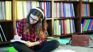 Girl writing, listening music and smiling to the camera in the library