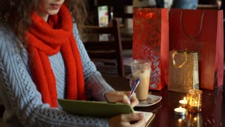 Girl writing something in notebook and drinking coffee in the cafe, steadycam sh