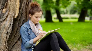 Girl writing something in notebook and smiling to the camera in the park