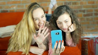 Girls lying on the sofa and having a videocall on smartphone